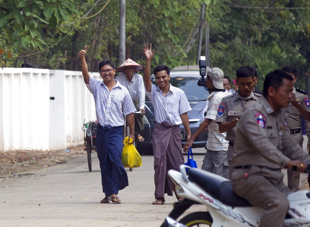 Reuters journalists Wa Lone, left, and Kyaw She Oo, third left, wave as they walk out from Insein Prison after being released in Yangon, Myanmar Tuesd...