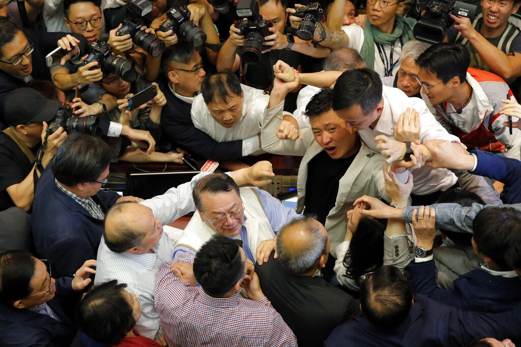 Pro-democracy and pro-Beijing lawmakers scuffle in the chamber at Legislative Council in Hong Kong, Saturday, May 11, 2019.