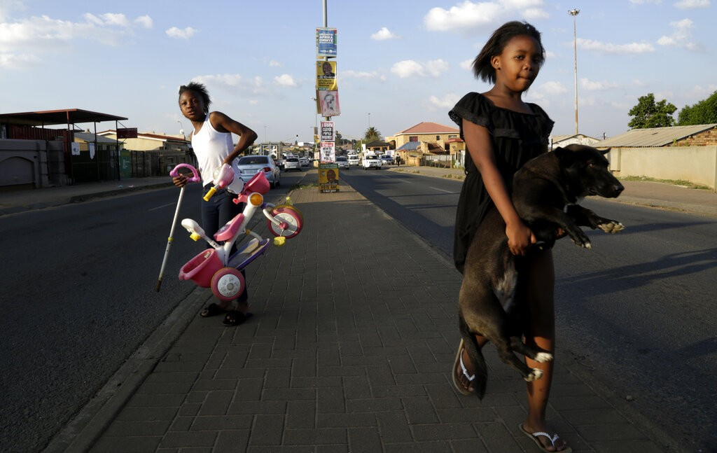 A young girl carries her dog as she crosses the main road, with headline from a newspaper and election posters on the streets of Soweto, South Africa,