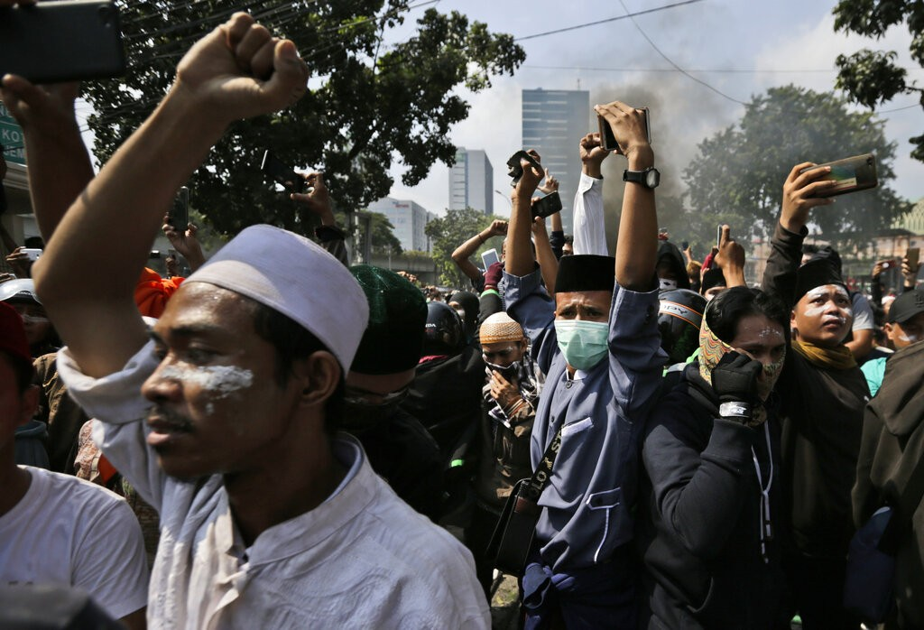 Protesters raise their fists as they taunt officers during a clash with the police in Jakarta, Indonesia, Wednesday, May 22, 2019.