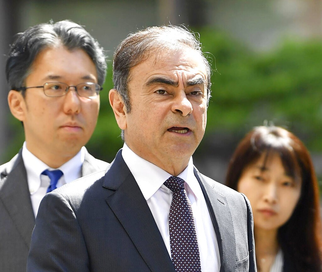 Former Nissan chairman Carlos Ghosn, center, arrives at Tokyo District Court for a pre-trial meeting in Tokyo Thursday, May 23, 2019.