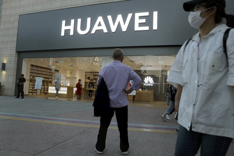 A man stands outside a Huawei store in Beijing.