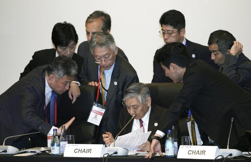 Bank of Japan Governor Haruhiko Kuroda, center bottom, speak with other participants June 8, 2019, in Fukuoka (AP Photo)