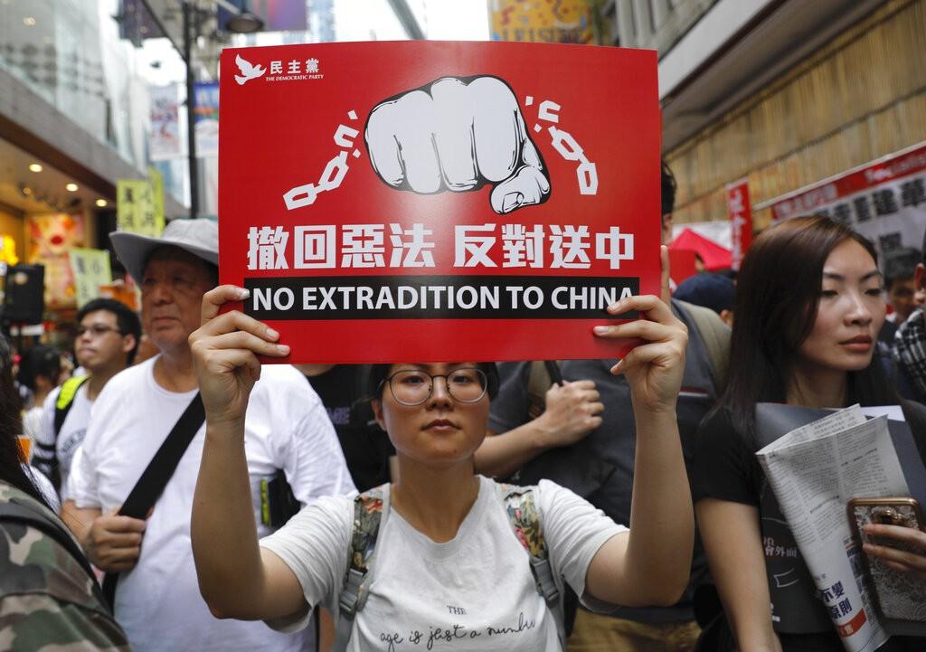 香港「反送中」遊行民眾舉牌並沿路高喊「撤回惡法,反對送中」的口號。(圖/美聯社)