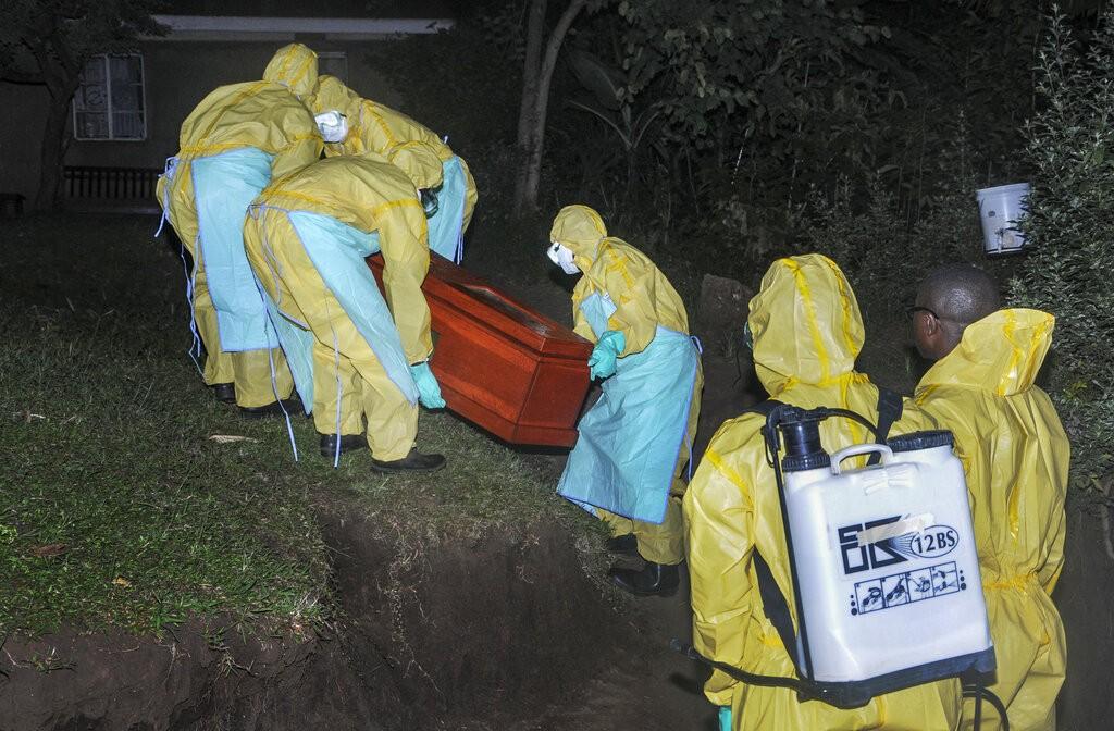 50歲的Agnes Mbambu為烏干達第二起感染伊波拉病毒死亡案例,穿著防護衣的衛生人員正預備將她的屍體掩埋。(圖/美聯社)