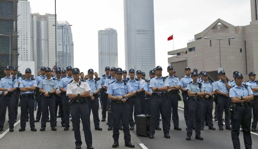 Hong Kong Police Officers stand in front of China Rep. office in HK, June 17