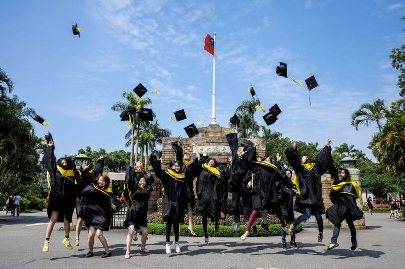Graduates throw their caps in the air in celebration at National Taiwan University (Photo/Taiwan Today)