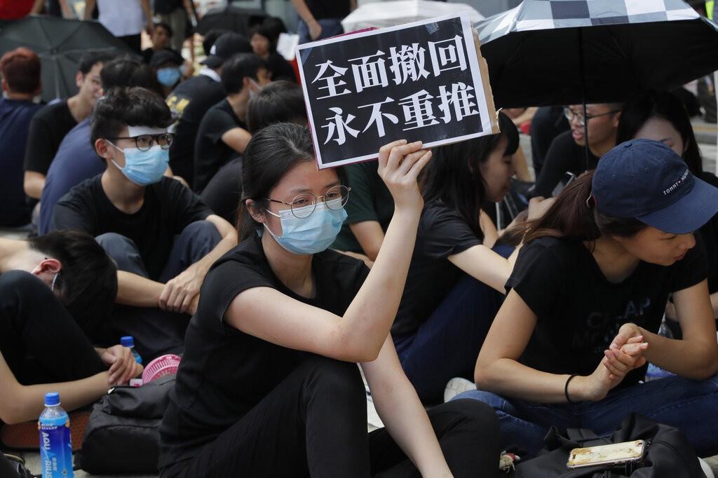 圖為21日集結在香港立法會外舉牌抗議之民眾(圖/美聯社)