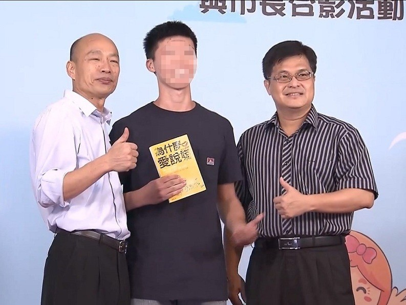 Student poses with Kaohsiung mayor holding book titled 'Why I love to lie'