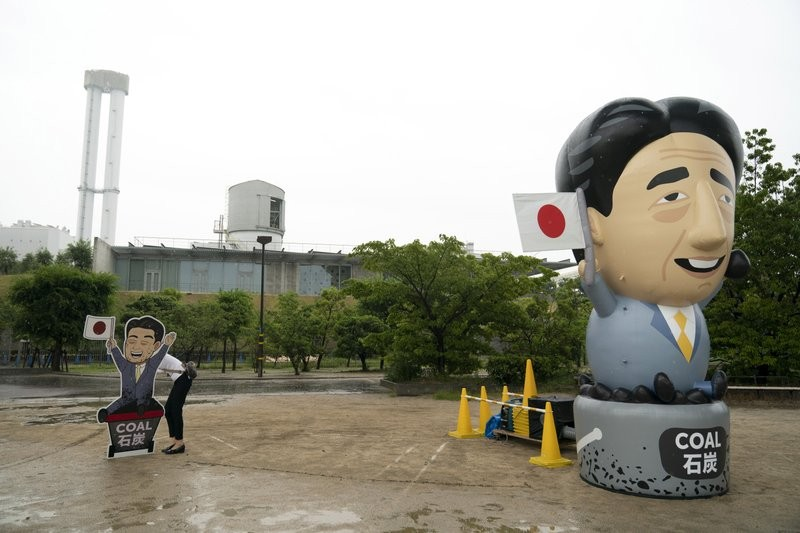An activist sets up a sign next to an inflatable depicting Japanese Prime Minister Shinzo Abe