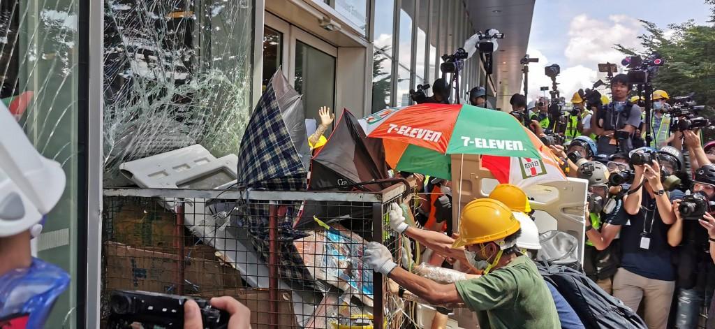 戴頭盔、手套、口罩的示威者1日下午撞破香港立法會 門,警方從裡面射胡椒噴劑,但阻擋不了衝擊。