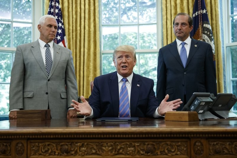 Donald Trump with Vice President Mike Pence (L) and Health Secretary Alex Azar (R) Monday, July 1