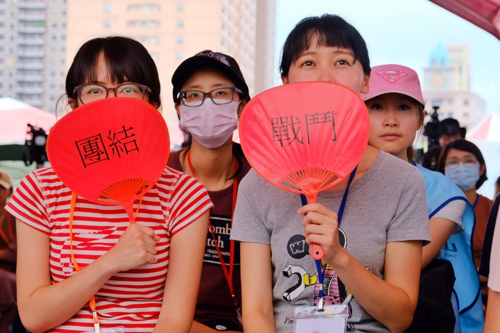 Striking EVA Air flight attendants with the words 'solidarity' and 'fight' on their fans.