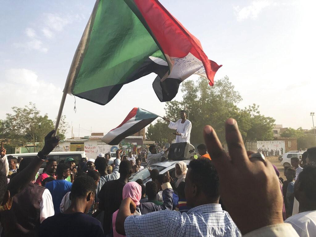 民眾揮舞著蘇丹國旗(來源 美聯社)