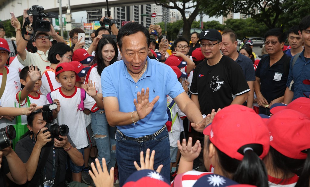 Terry Gou (center, in blue) on his way to a baseball match Saturday July 6.