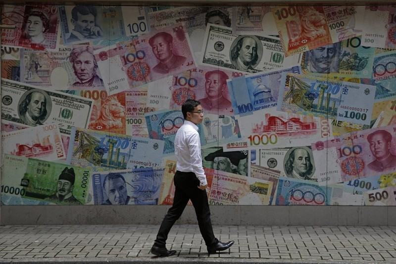 A man walks past a money exchange shop at Central, a business district of Hong Kong. (AP photo)