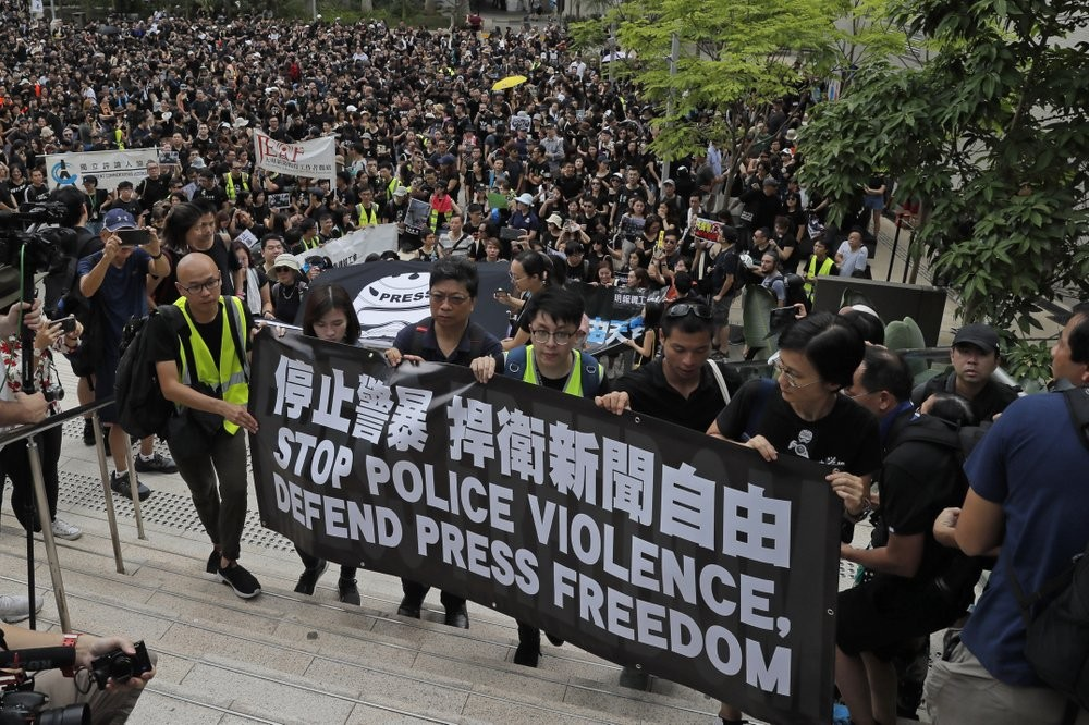 Journalists march to police headquarters and government headquarters in Hong Kong, July 14