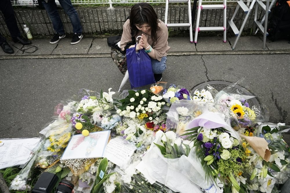 A woman prays for the victims of the arson attack on Kyoto Animation Studios.