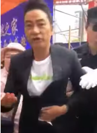 Hong Kong actor Simon Yam being led away from the scene after the attack Saturday morning. (screenshot from YouTube)