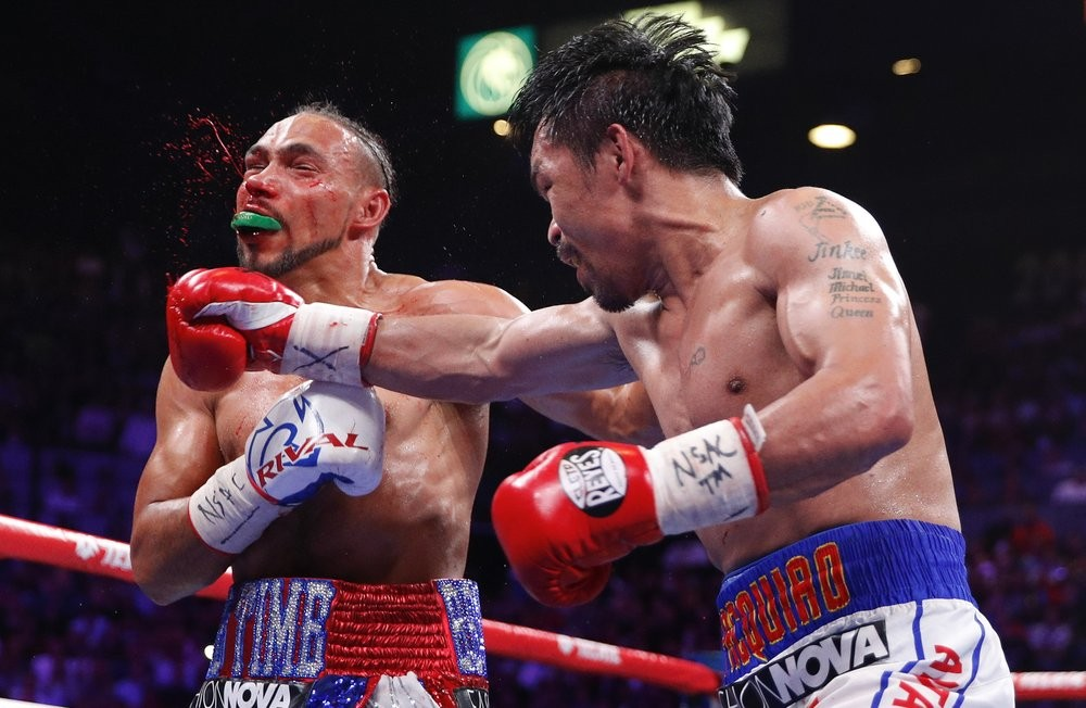 Manny Pacquiao, right, lands a punch against Keith Thurman in the fifth round during a welterweight title fight Saturday, July 20, 2019, in Las Vegas....