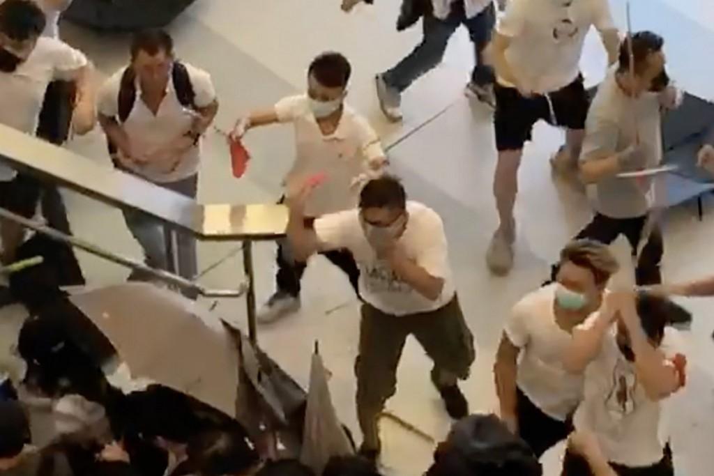 Screenshot showing men in white shirts hitting passengers.