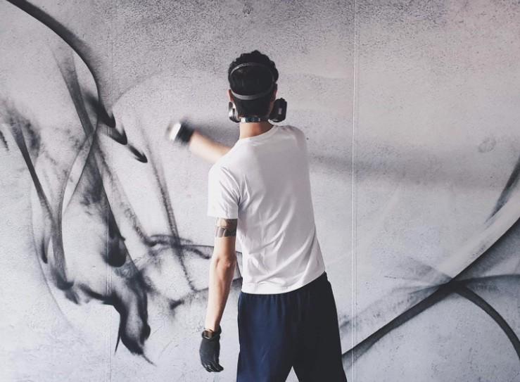 DEBE paints a mural.  (DEBE Facebook photo)