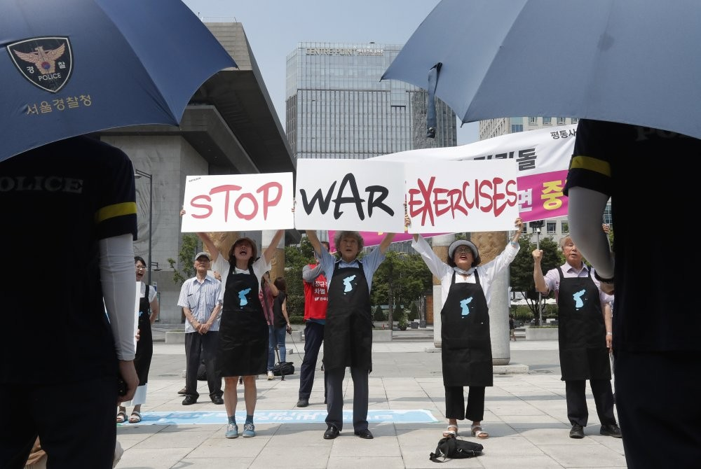 Protesters hold up placards to oppose planned joint military exercises between South Korea and the United States near the U.S. embassy in Seoul, South