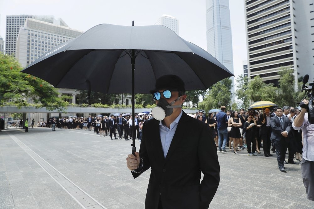 A man carries an umbrella and wears a face mask as lawyers gather for a protest march in Hong Kong Aug. 7 (AP photo)