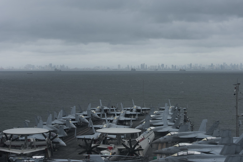 Fighter jets and recon aircraft aboard USS Ronald Reagan with Manila in distance, Aug. 7 (US Navy photo)