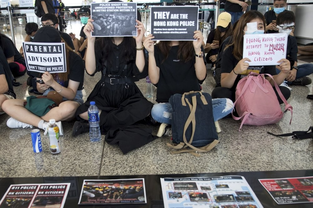 Protesters at Hong Kong International Airport Tuesday August 13 denounce police violence.
