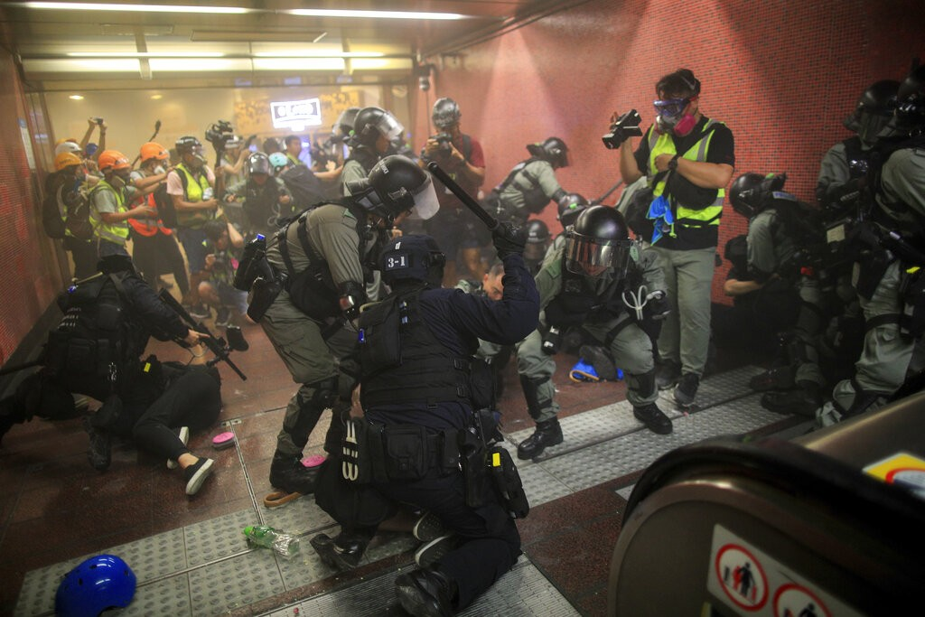 Police charge protesters inside MTR station on Aug. 11 (Source: AP)