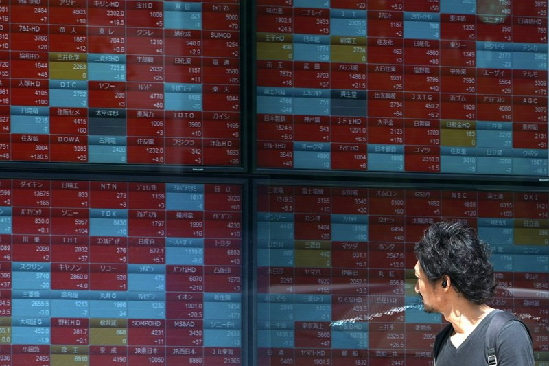 A man looks at an electronic stock board showing Japan's Nikkei 225 index (AP photo)
