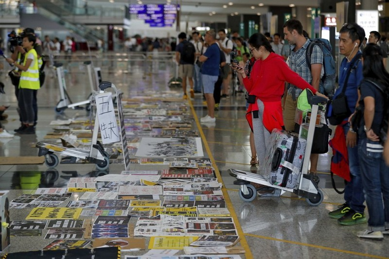 Travellers look at placards and posters placed by protesters at the airport in Hong Kong (AP photo)
