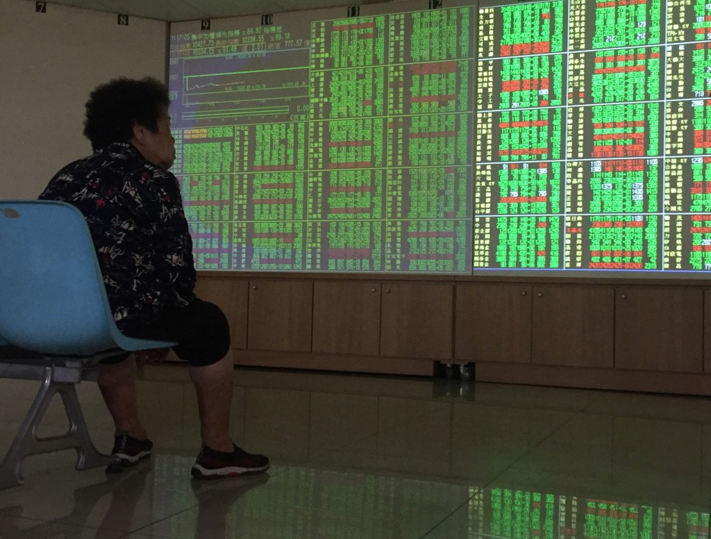 An investor watches stock market fluctuations in Taipei Thursday August 15.