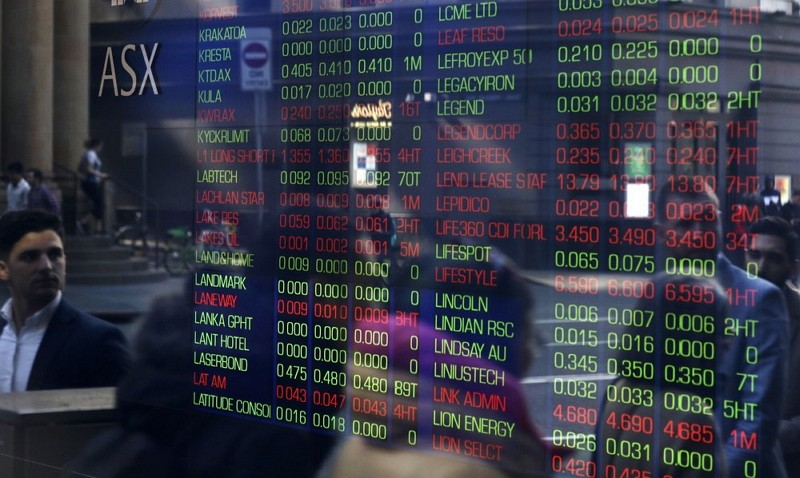 People are reflected in a window as they walk past the Australian Stock Exchange in Sydney (AP photo)