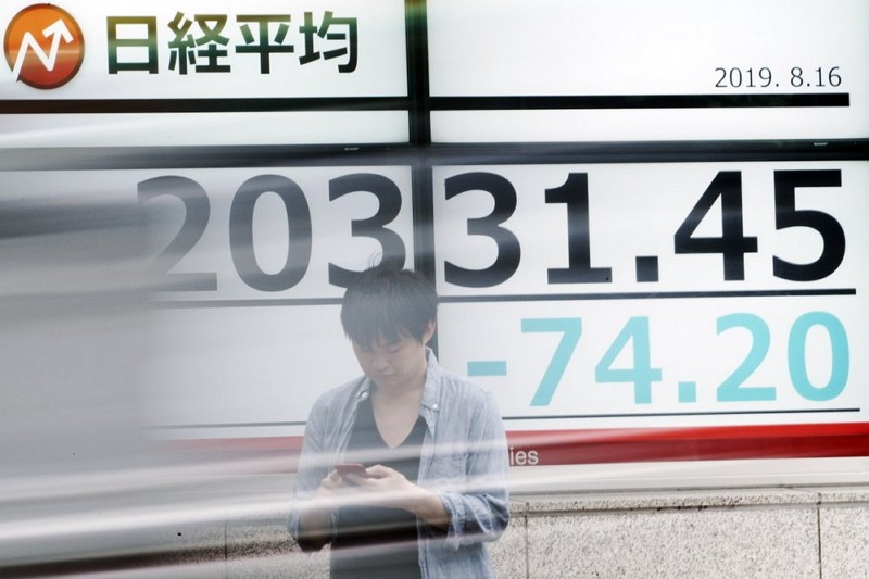 A man stands as a car goes by an electronic stock board showing Japan's Nikkei 225 index. (AP photo)
