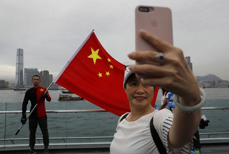 Pro-China supporters take a selfie with a Chinese national flag to support police during a rally at a park in Hong Kong. (AP photo)