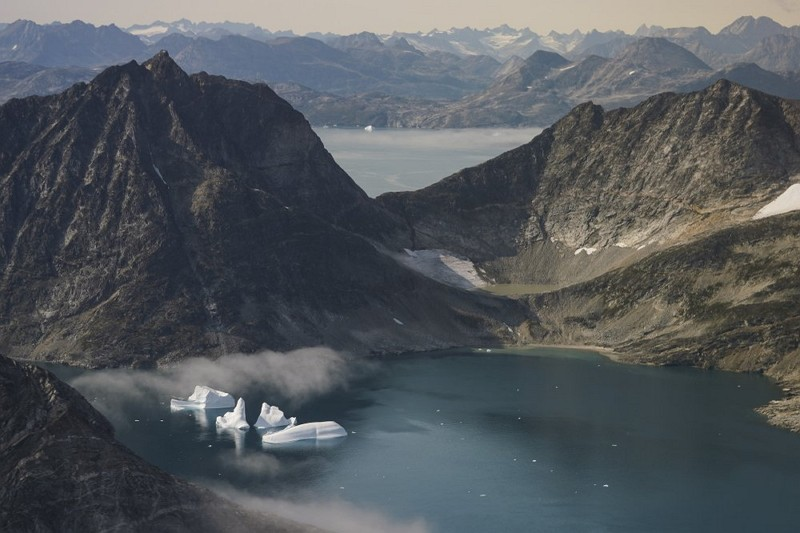 Icebergs are photographed from the window of an airplane carrying NASA scientists as they fly on a mission to track melting ice in eastern Greenland (