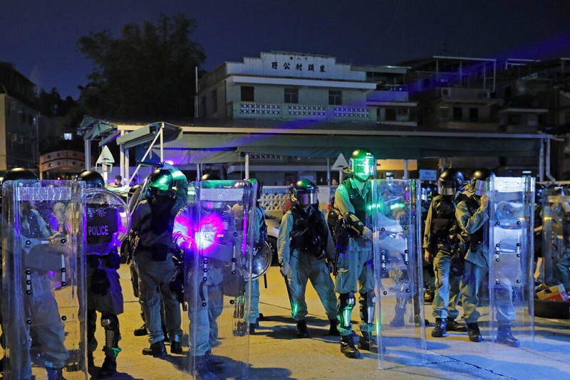 Riot police are illuminated by laser pointers from protesters during a protest at the Yuen Long MTR station in Hong Kong (AP photo)