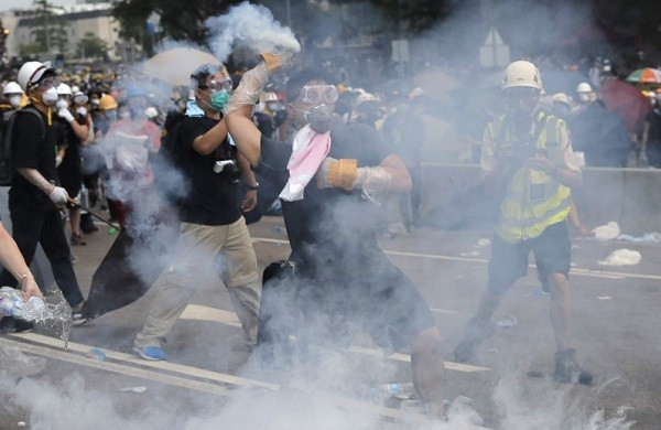 Protester hurls tear gas canister back at police outside Hong Kong's Legislative Council