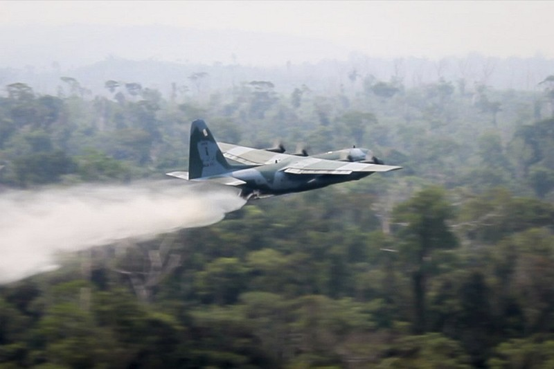 A C-130 Hercules aircraft dumps water to fight fires burning in the Amazon rainforest (AP photo)