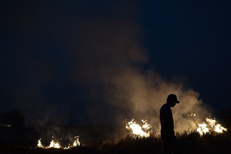 Neri dos Santos Silva, center, is silhouetted against an encroaching fire threat after he spent hours digging trenches to keep the flames from spreadi...