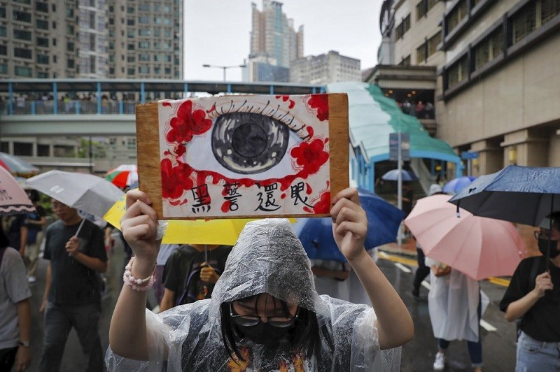 """A woman holds a placard that reads """"Corrupt police return eyes to the victims"""" as demonstrators march in the rain in Hong Kong, Sunday, Aug. 25, 2019."""