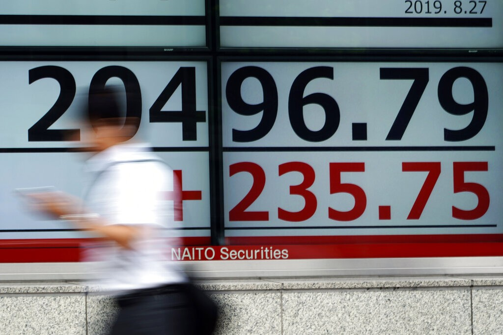 A man walks past an electronic stock board showing Japan's Nikkei 225 index at a securities firm in Tokyo Tuesday, Aug. 27, 2019.