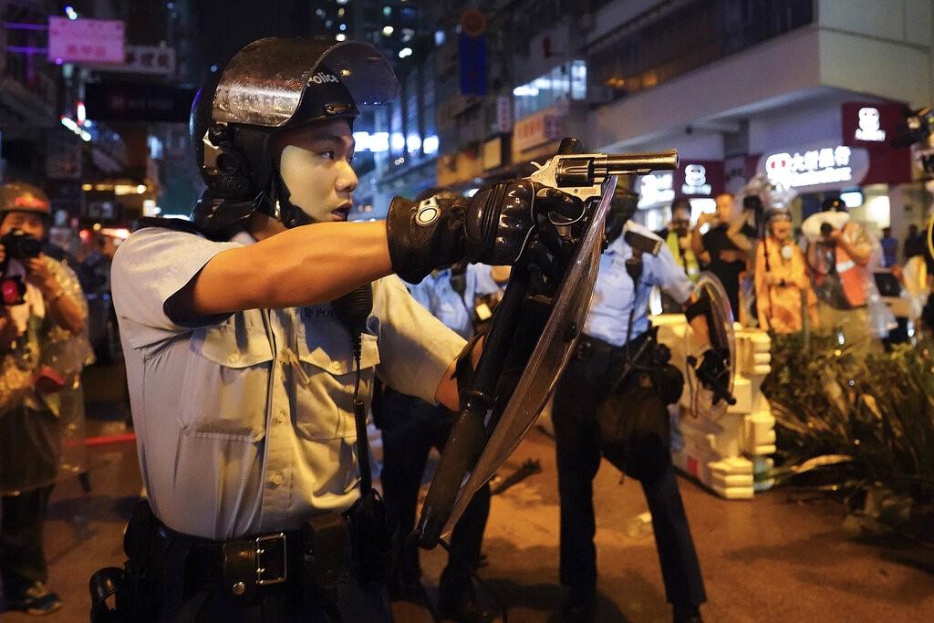 Hong Kong policeman points a pistol at protesters