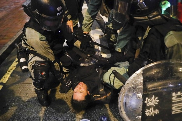 Police arrest Hong Kong protester.