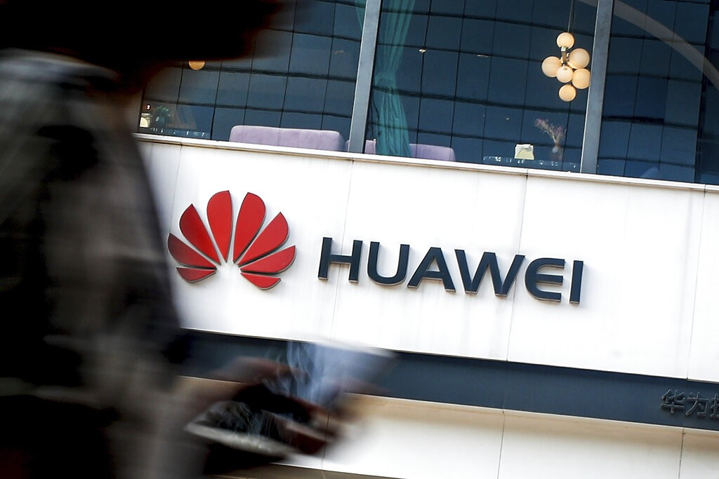 FILE - In this July 30, 2019, file photo a woman walks by a Huawei retail store in Beijing.