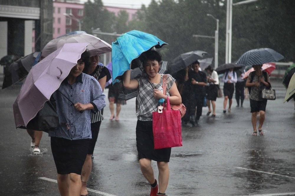 Pedestrians battle wind and rain in Pyongyang, Nor...