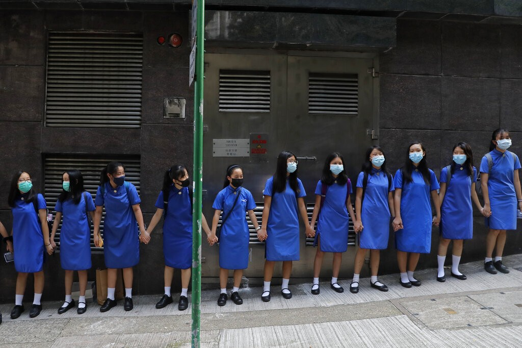 Students wearing mask hold hands to surround St. Stephen's Girls' College in Hong Kong, Monday, Sept. 9, 2019.