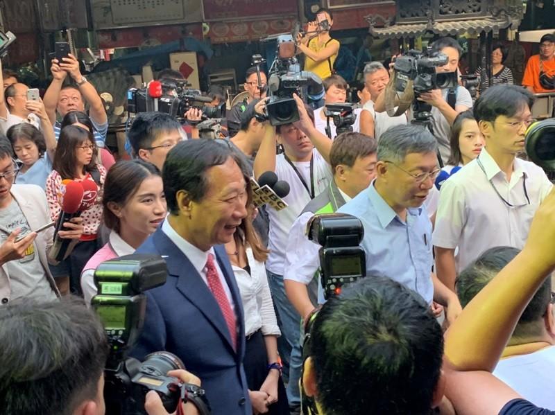 台北市長柯文哲(前右2)與鴻海創辦人郭台銘(前左)11日到新竹都城隍廟參拜,吸引大批媒體。中央社